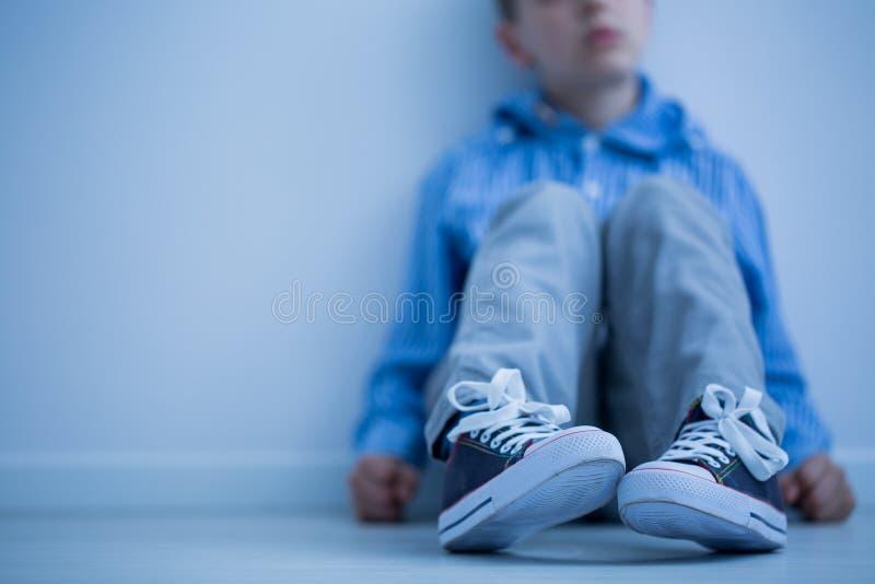 Garçon s'asseyant sur un plancher photo libre de droits