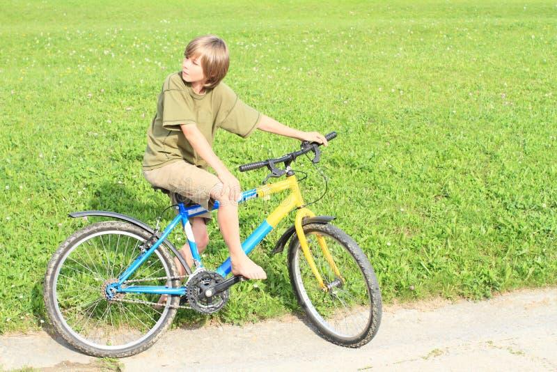 Garçon s'asseyant sur un vélo photo libre de droits