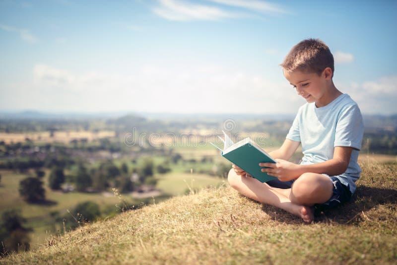 Garçon s'asseyant sur une colline lisant un livre dans un pré images stock