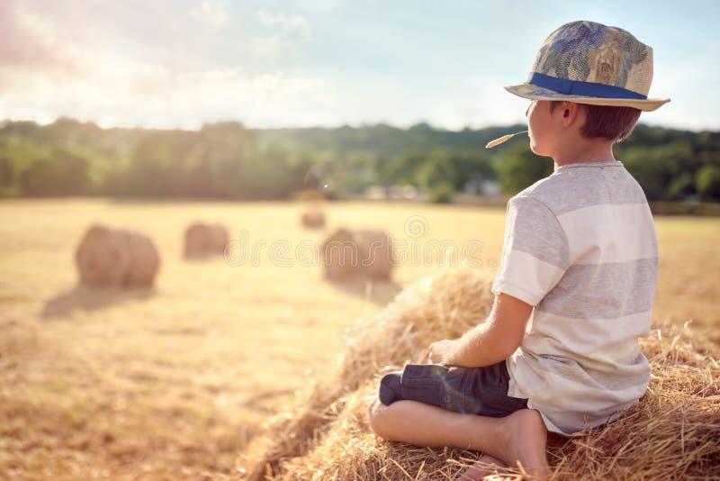 Garçon s'asseyant sur une meule de foin en été observant le coucher du soleil photos stock