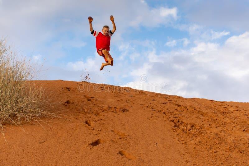 Garçon sautant outre des dunes de sable oranges avec un fond lumineux de ciel bleu photographie stock libre de droits