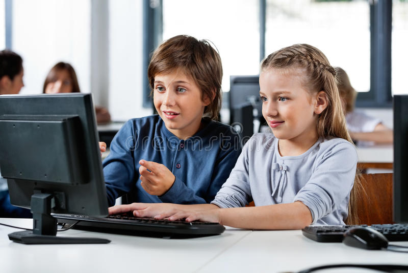 Garçon se dirigeant tout en à l'aide du PC de bureau avec l'ami à image stock
