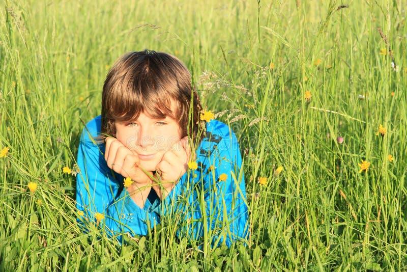 Garçon se situant dans l'herbe photo stock