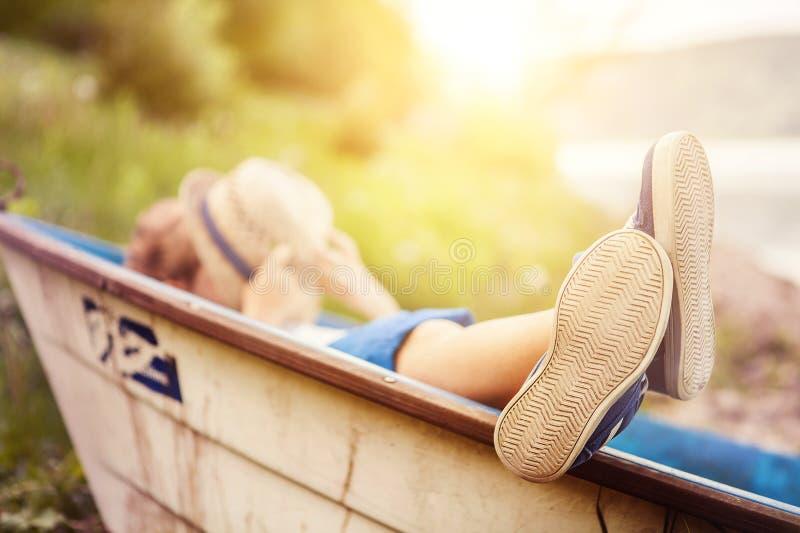 Garçon se situant dans le vieux bateau dans la fin de côte de lac vers le haut de l'image images libres de droits
