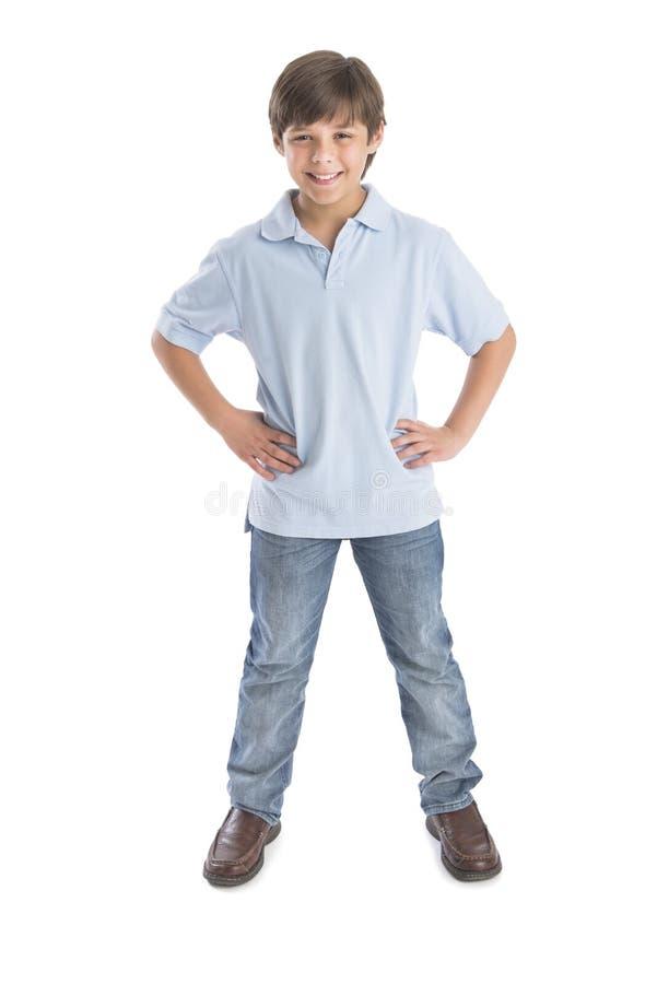 Garçon se tenant avec des mains sur la hanche sur le fond blanc photos libres de droits