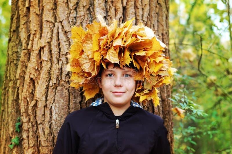 Garçon se tenant en parc d'automne sur un fond des arbres À la tête de la guirlande tissée des feuilles d'automne photo libre de droits