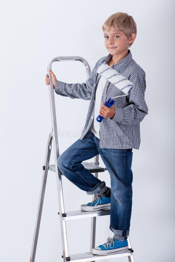 Garçon se tenant sur l'échelle avec le rouleau de peinture images stock