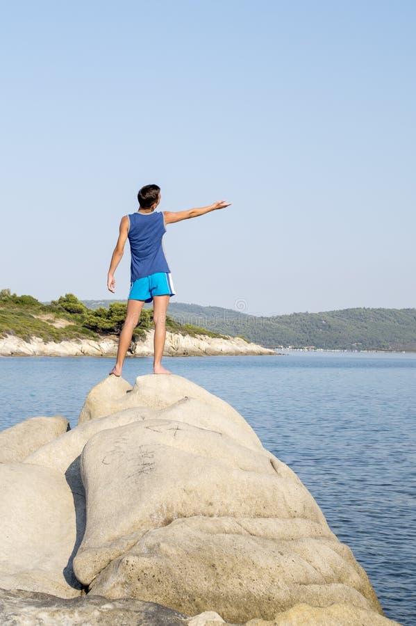 Garçon se tenant sur une roche à côté de la mer image stock