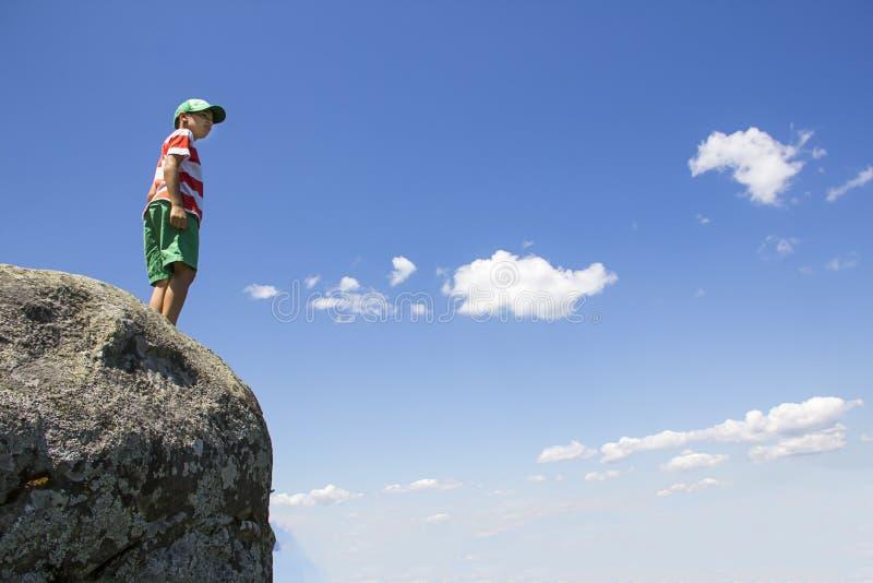 Garçon se tenant sur une roche avec un ciel bleu photos stock