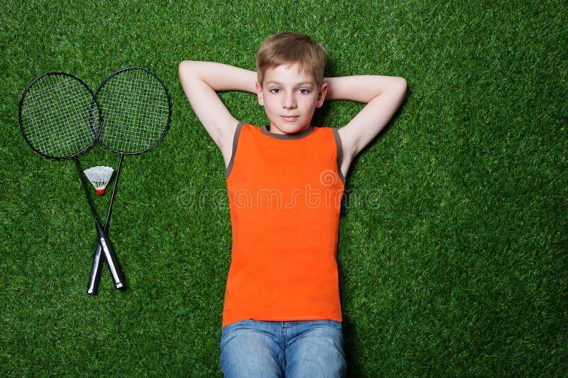 Garçon se trouvant avec la raquette de badminton sur l'herbe verte images stock