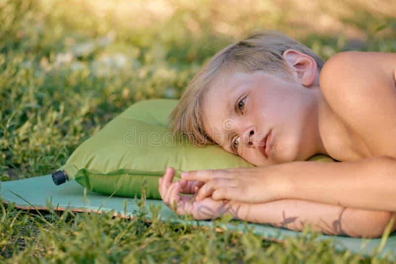 Garçon se trouvant sur l'herbe photo stock