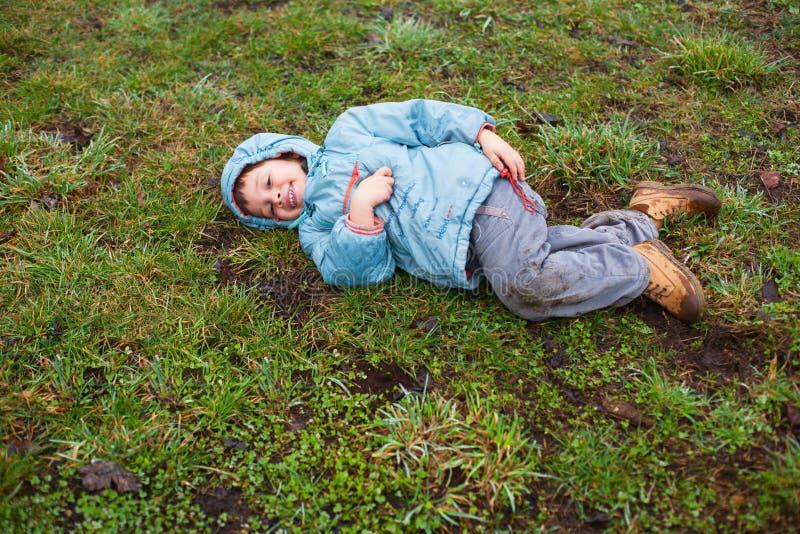 Garçon se trouvant sur l'herbe images stock