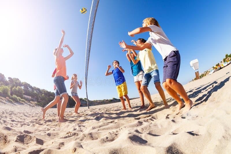 Garçon servant la boule pendant le match de volleyball de plage photographie stock libre de droits