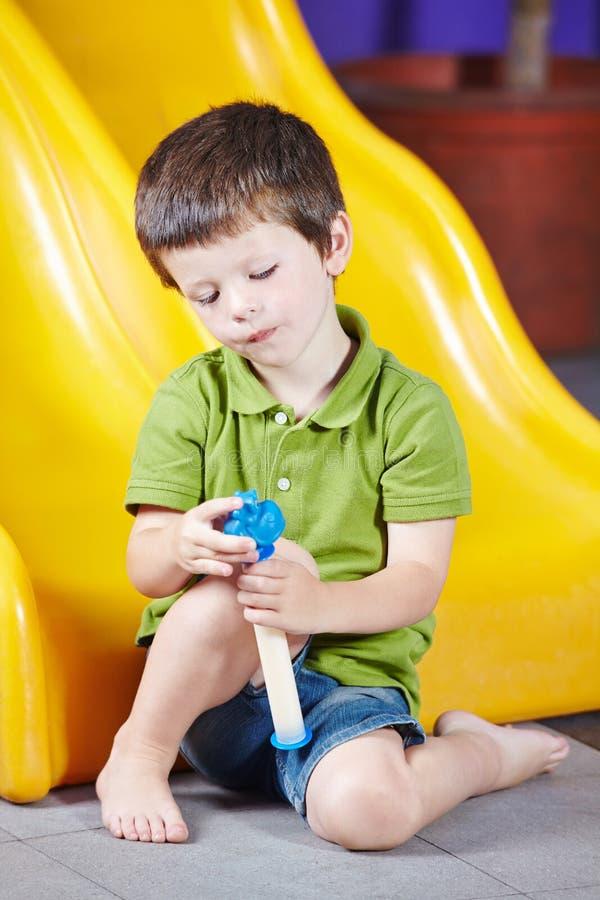 Garçon seul jouant dans le jardin d'enfants photos libres de droits