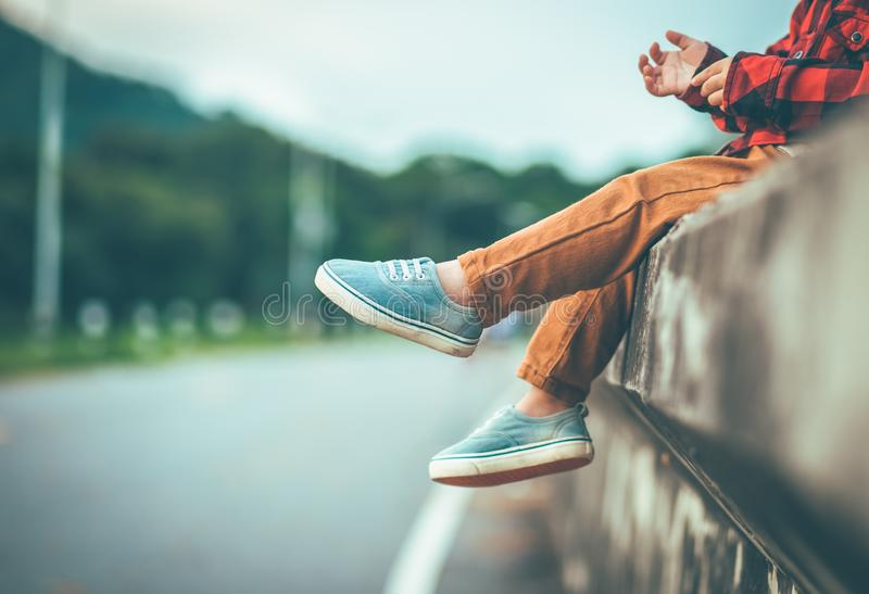 Garçon seul s'asseyant avec ses pieds se dirigeant vers le bas dans le ton de cru images stock