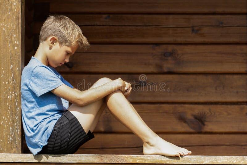 Garçon seul triste s'asseyant dehors photo stock