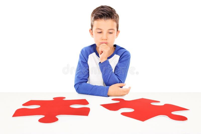 Garçon songeur regardant deux morceaux de puzzle photos libres de droits