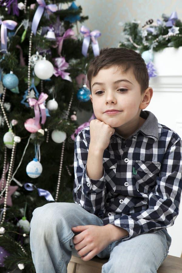 Garçon songeur s'asseyant près de l'arbre de Noël images libres de droits