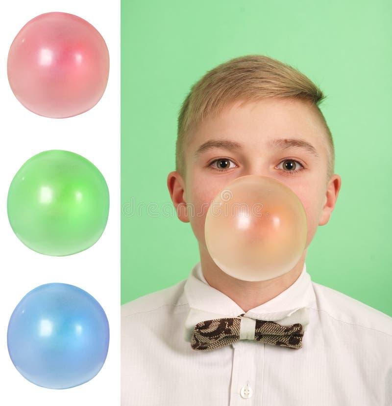 Garçon soufflant une bulle de bubblegum Plus trois en blanc photo libre de droits