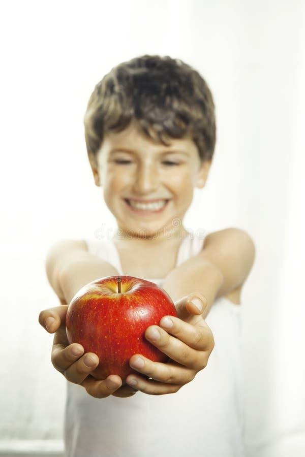 Garçon souriant avec la pomme rouge photographie stock libre de droits