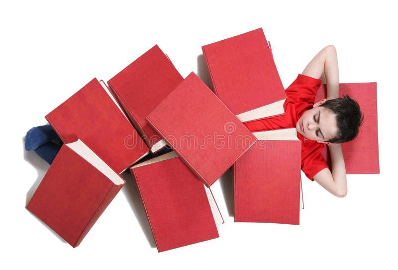 Garçon sous les livres rouges photo stock