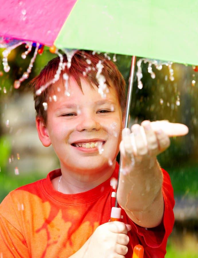 Garçon sous un parapluie pendant une pluie photo stock
