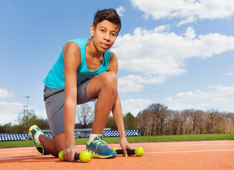 Garçon sportif adolescent prenant des haltères dans le stade photos stock
