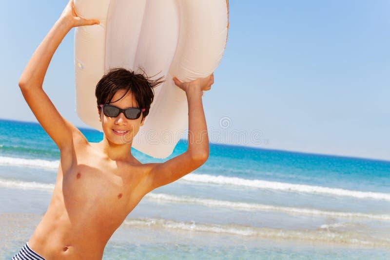 Garçon sportif avec le matelas d'air de natation au-dessus images stock