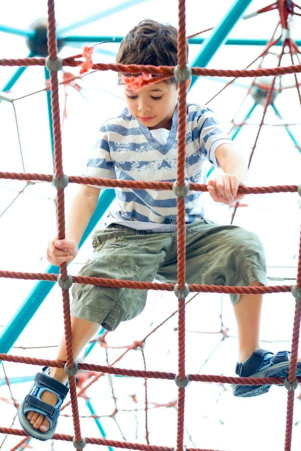 garçon sur l'activité de corde dans la cour de jeu. images libres de droits