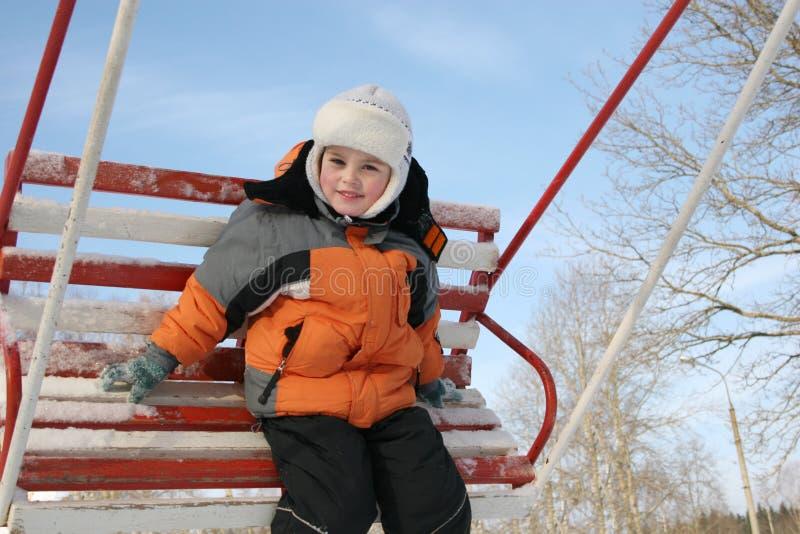Garçon sur la balançoir de l'hiver image stock