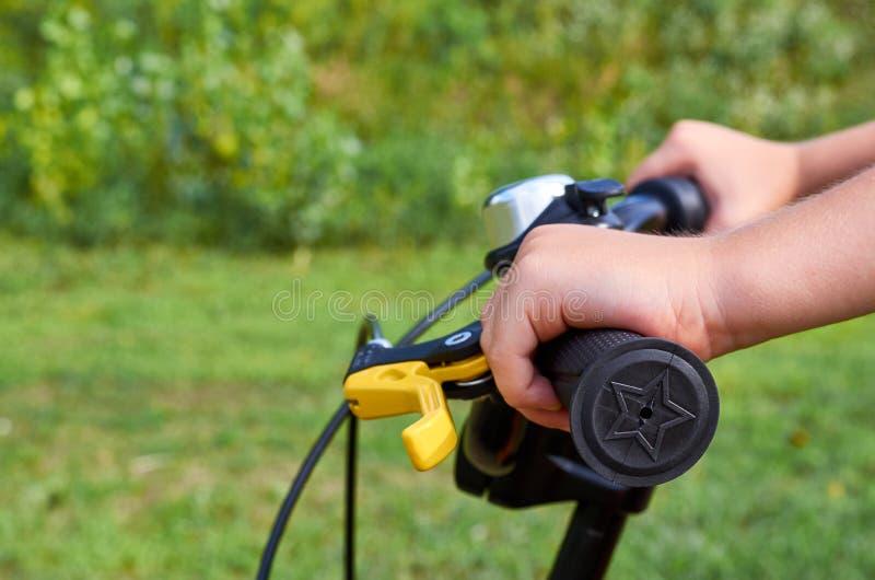 Garçon sur la bicyclette jaune d'enfants en parc, le gouvernail de direction avec des freins et les mains images libres de droits