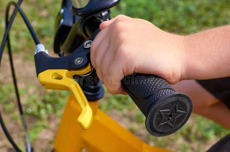 Garçon sur la bicyclette jaune d'enfants en parc, le gouvernail de direction avec des freins et les mains photographie stock