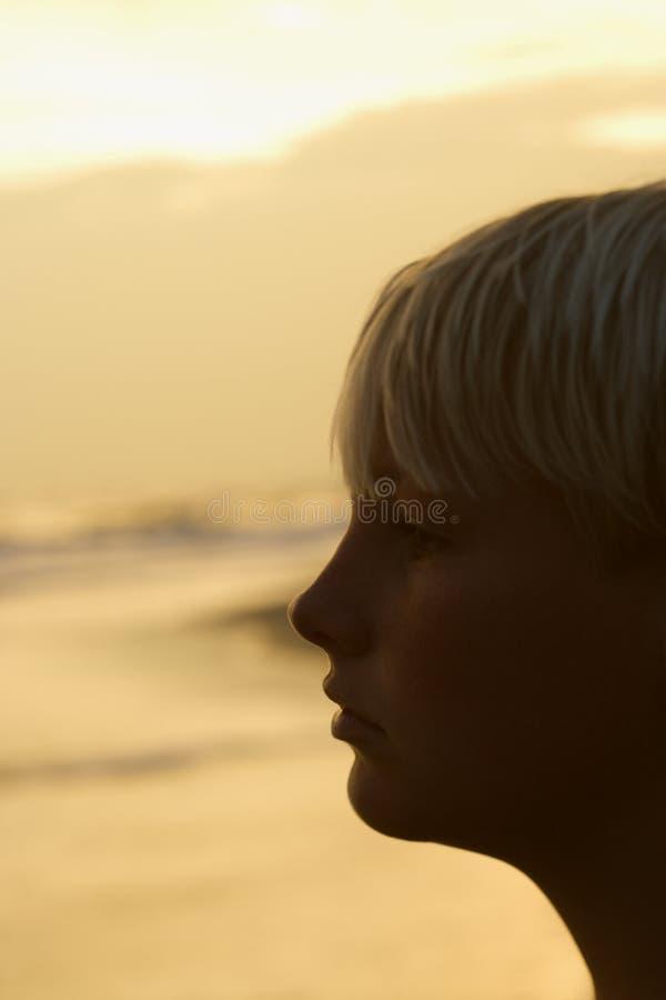 Garçon sur la plage au coucher du soleil image stock