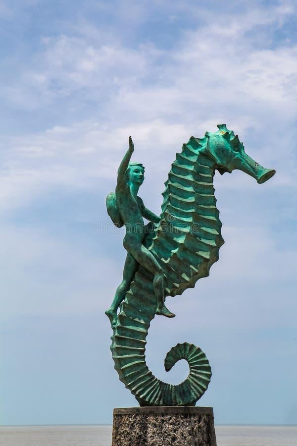 Garçon sur la sculpture en hippocampe dans Puerto Vallarta au Mexique photo stock