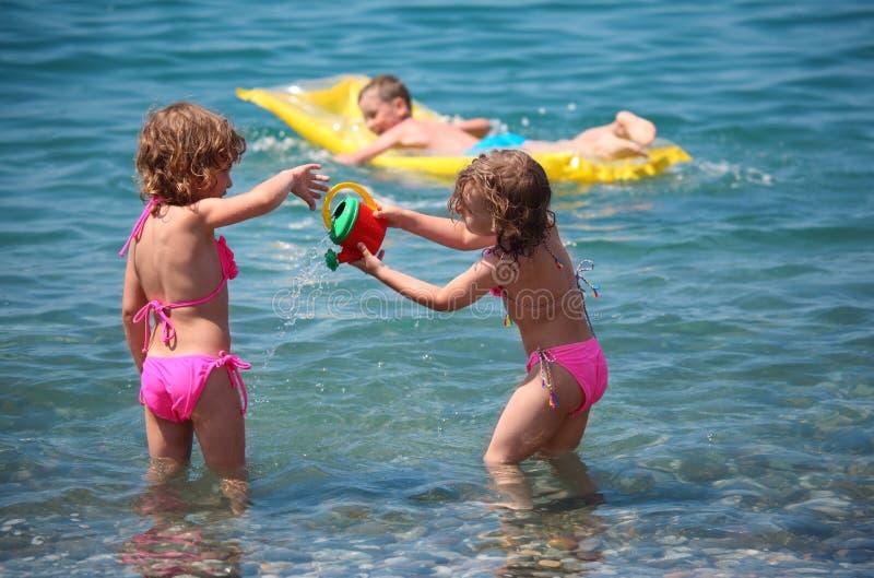 Garçon sur le matelas gonflable dans la mer et les filles tout près images libres de droits
