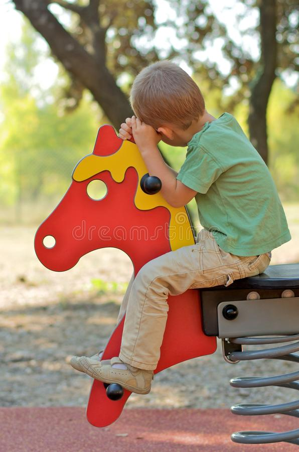 Garçon sur un cheval sur une cour de jeu images libres de droits