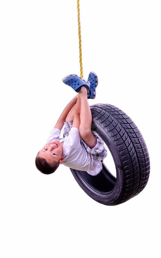 Garçon sur une oscillation de pneu image libre de droits