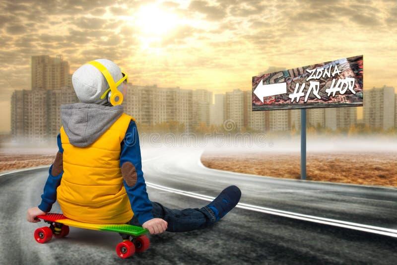 Garçon sur une planche à roulettes, raie sur la route Le petit garçon dans le style du hip-hop Le jeune frappeur Refroidissez le  image stock