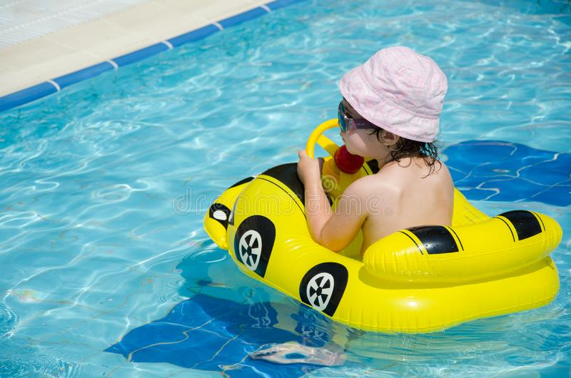 Garçon sur une voiture jaune gonflable dans la piscine photo stock