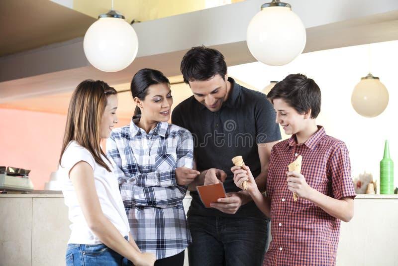 Garçon tenant des cônes tandis que famille choisissant la crème glacée du menu photographie stock libre de droits