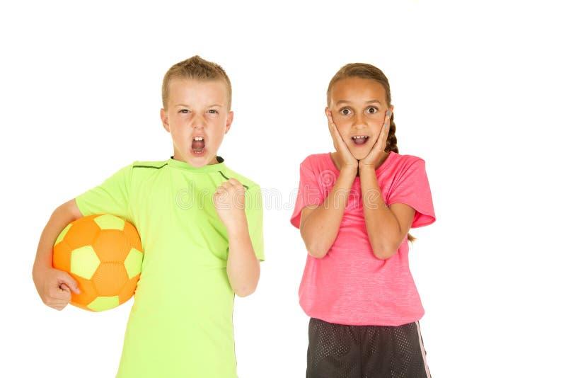 Garçon tenant la fille de ballon de football avec l'expression du visage enthousiaste photos libres de droits