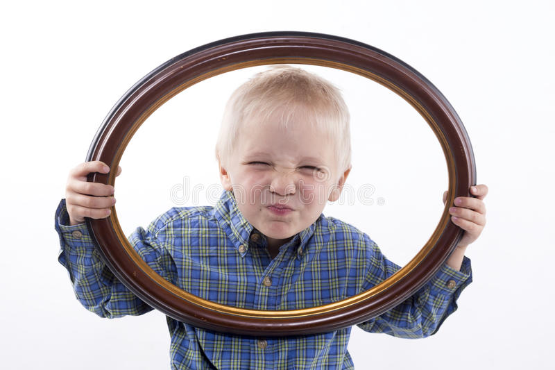 Garçon tenant le cadre photo libre de droits