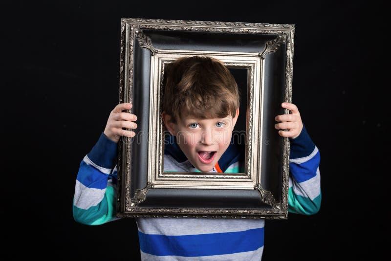 Garçon tenant le cadre de tableau photos stock