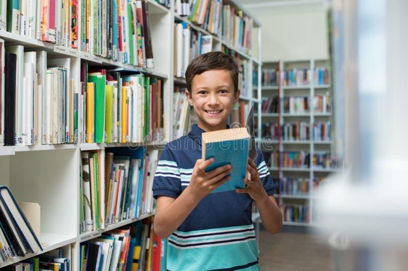 Garçon tenant le livre dans la bibliothèque à l'école photos stock