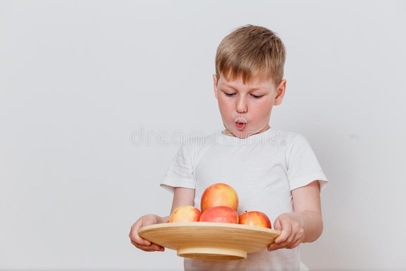 Garçon tenant un plat avec des pommes images libres de droits