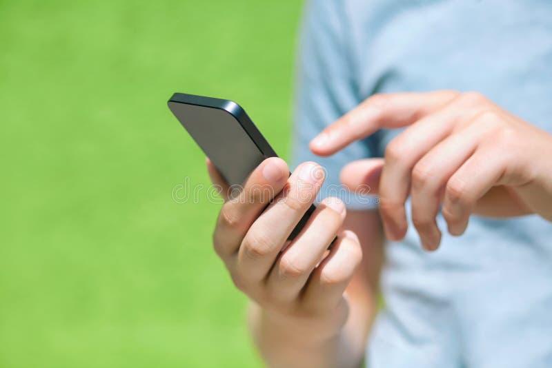 Garçon tenant un téléphone et un écran tactile pour le doigt contre un gree image libre de droits