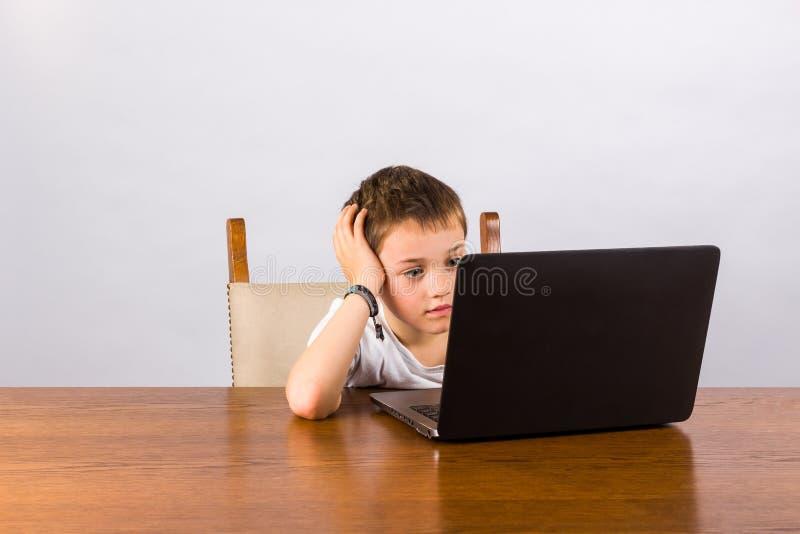 Garçon travaillant sur l'ordinateur portatif photographie stock libre de droits