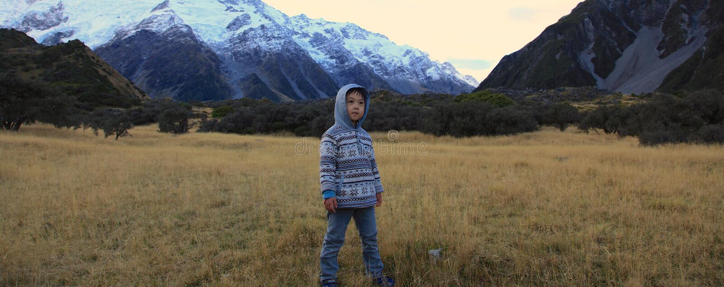 Garçon trimardant dans les montagnes photographie stock
