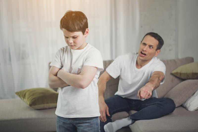 Garçon triste écoutant des cris perçants fâchés de papa photographie stock libre de droits