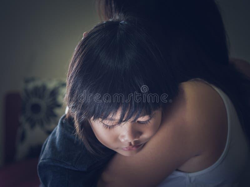 Garçon triste de plan rapproché petit étreint par sa mère à la maison images libres de droits